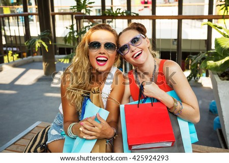Outdoors fashion portrait of two young beautiful women friends in shopping mall with a lot of shopping bags. Smiling and and happy after successful shopping. Wearing stylish t-shirts and sunglasses.  - stock photo