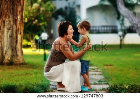outdoors in the park mother and son on a walk hug - stock photo