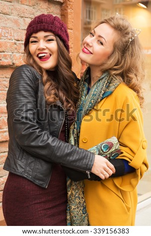 Outdoors lifestyle fashion portrait of two pretty cheerful girls friends. Smiling and walking on the autumn city. Wearing stylish outerwear, hat and sunglasses. Close up. Autumn colors. Joy, fun  - stock photo