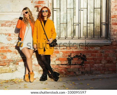 Outdoors lifestyle fashion portrait of two sexy girls friends, walking on the autumn city. Posing at an old wall. Wearing stylish bright outerwear with handbags and sunglasses. Autumn colors - stock photo