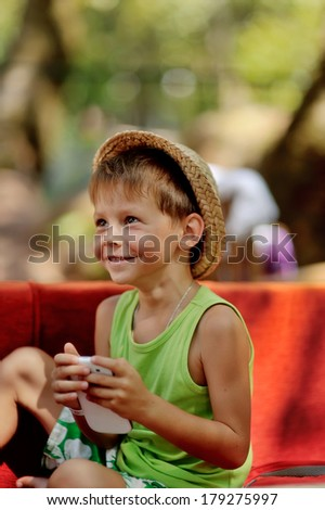Outdoors on a red couch resting fun boy in a hat with phone - stock photo