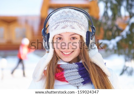 Outdoors on a winter day. Girl listen music. - stock photo