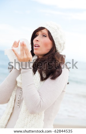 outdoors on the beach standing female sneezing in tissue wearing scarf and warm clothes feeling sick - stock photo