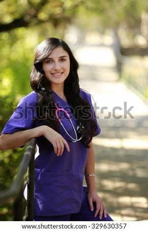 Outdoors portrait of beautiful hispanic nurse/doctor - stock photo