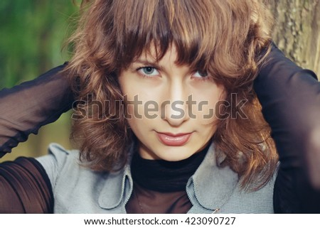 Outdoors portrait of beautiful young brunette woman looking at camera. - stock photo