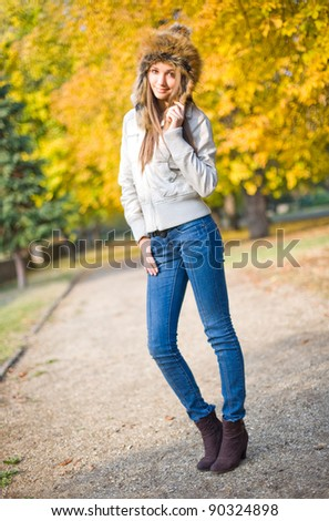 Outdoors portrait of fashionable young brunette wearing russian style fur hat. - stock photo