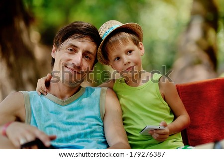 Outdoors portrait of father and son in a straw hat - stock photo