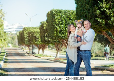 outdoors portrait of happy family wearing casual. Mom and dad holding little kid with funny hat. - stock photo