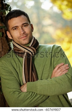 Outdoors portrait of happy young man standing in autumn park at tree.? - stock photo
