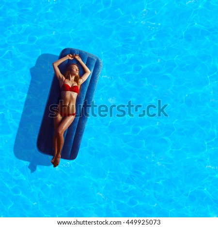 outdoors portrait of hot young lady in red bikini sunbathing by the blue pool - stock photo