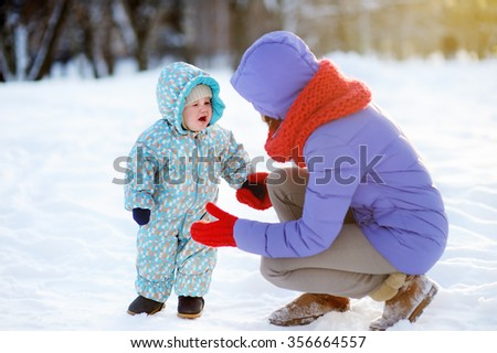 Outdoors portrait of young mother and her crying toddler child  - stock photo