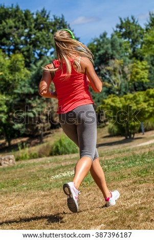outdoors sports - back view of an athletic young blond woman running and exercising outdoor in sunny day - stock photo