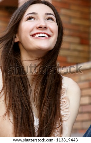 Outdoors street portrait of beautiful young brunette happy smiling teen girl - stock photo