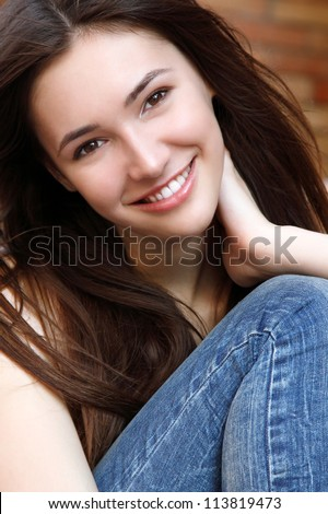 Outdoors street portrait of beautiful young brunette smiling teen girl - stock photo