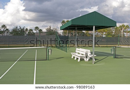 Outdoors tennis court on a sunny and cloudy day. - stock photo