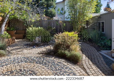 Outdoors with arched cobblestone with walkways, greenery and water fountain.   - stock photo