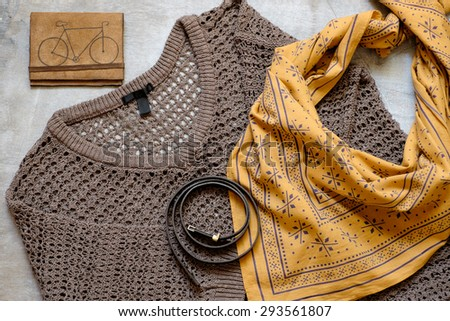 Outfit of casual woman. Brown sweater and a yellow scarf leather wallet belt on a wooden background. - stock photo