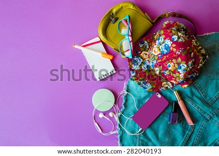 Outfit of  hipster teenager, young woman or girl . Overhead of essentials for modern young  stylish person. Different objects on purple background . Area view. - stock photo