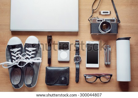 Outfit of modern traveler, student, woman or guy. Overhead of essentials on wooden background: camera, smartphone, glasses, flashlight, laptop, wallet, watch, gumshoes, thermos, mult itool, mp3 player - stock photo