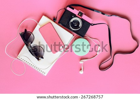 Outfit of student, teenager, young woman or girl . Overhead of essentials for modern young person. Different objects on  pink background . Pastel  tender colors. Area view. - stock photo