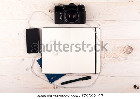 Outfit of traveler on a white wooden background - stock photo