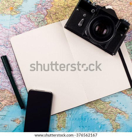 Outfit of traveler on map background - stock photo