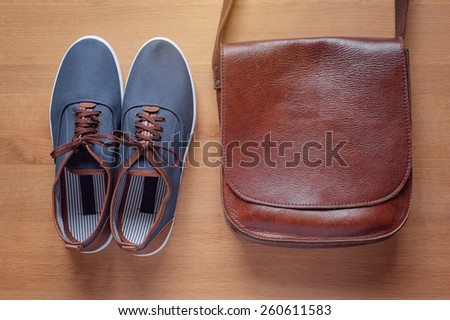 Outfit of traveler, student, teenager, young man. Overhead of essentials for modern young person. objects on wooden background  include gumshoes and leather bag. - stock photo