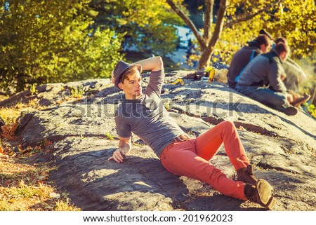 Outing in Autumn. Dressing in a gray long sleeves with roll-tab Henley shirt, red jeans, brown boot shoes, wearing a woolen Fedora hat, a young man is sitting on rocks under sunshine, relaxing.  - stock photo