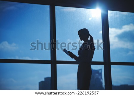 Outline of businesswoman with touchpad networking by the window in office - stock photo
