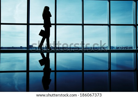 Outline of office worker with briefcase speaking on the phone by the window - stock photo