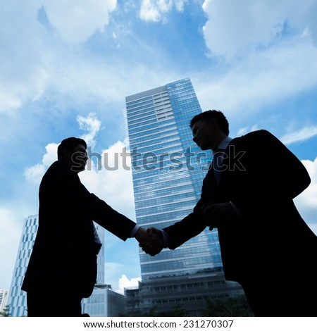 Outlines of businesspeople handshaking after a deal - stock photo