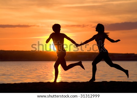 Outlines of happy guy and girl running down seashore at sunset - stock photo