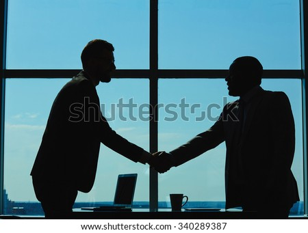 Outlines of two businessmen handshaking against window - stock photo