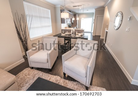 Outlook at the luxury modern living suite : dining room and the kitchen at the back with two modern chairs in front of.  Interior design of a brand new townhouse. - stock photo