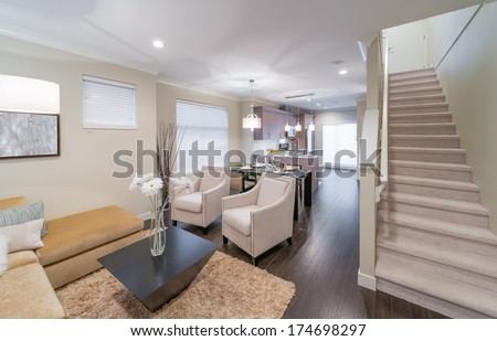Outlook at the luxury modern living suite : living room, dining room and the kitchen at the back with two modern chairs in front of. Interior design of a brand new townhouse. - stock photo