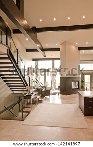 Outlook at the luxury spacious modern living room with the fireplace and stairs to the upper level. Interior design. Vertical. - stock photo