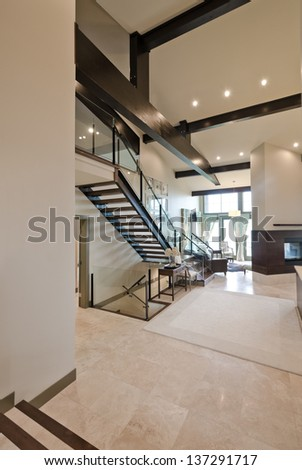Outlook at the luxury spacious  modern room with the  fireplace and stairs to the upper level. Interior design. Vertical. - stock photo