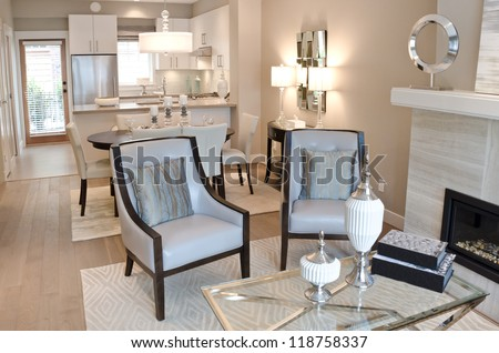 Outlook of the luxury living suite : dining room and the kitchen at the back with two modern leather chairs in front of - stock photo