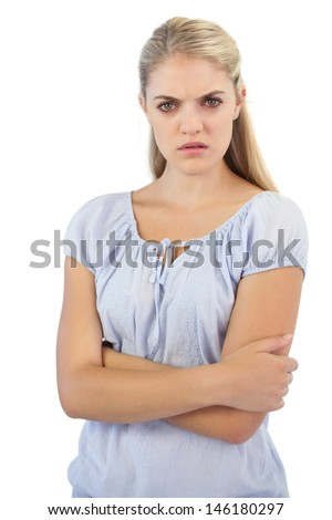 Outraged blonde woman  with arms crossed on white background - stock photo