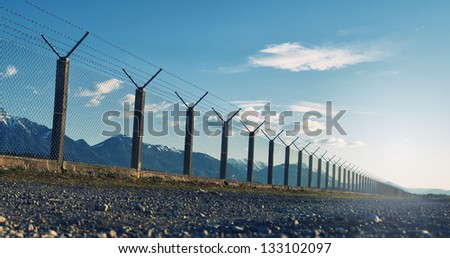 Outside barbed wire fence with blue sky. - stock photo
