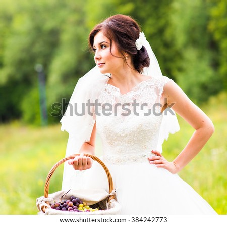Outside portrait of beautiful young bride with basket in a park - stock photo