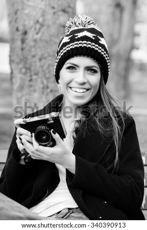 Outside portrait of cheerful attractive brunette girl with photo camera in her hand. Wearing cozy knitted beanie and jacket. Nature background - stock photo