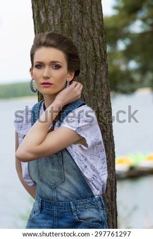 outside portrait of sexy young woman with braid hair-style, denim overalls and trendy t-shirt posing near tree with lake water on background.  - stock photo