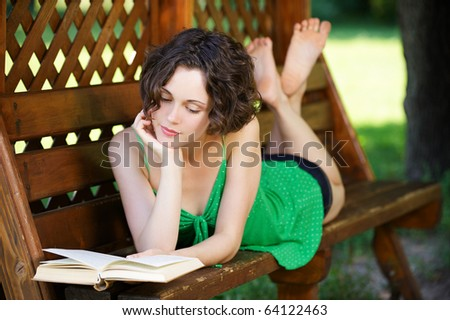 outside portrait of young beautiful curly woman laying on bench and reading book in park - stock photo