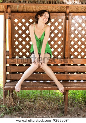 outside portrait of young beautiful curly woman sitting on wooden bench with bare legs in park - stock photo