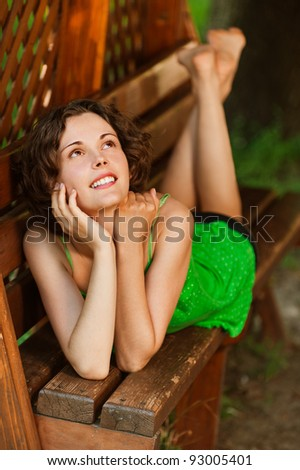 outside portrait of young beautiful happy woman laying on bench in park - stock photo