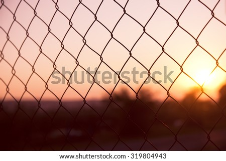 Outside rusty wire fence with beautiful sunset. Wire fence barricade closeup background. - stock photo