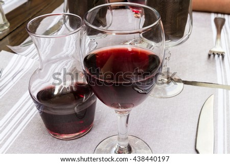 Outside table laid for eating with carafe and glass of red wine. - stock photo