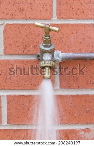 Outside tap on brick wall wasting water - stock photo