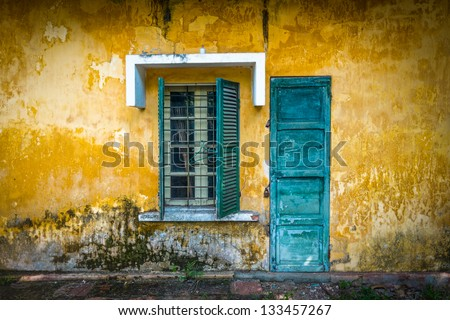 Outside view of deserted house with details in Vietnam. Old and grungy yellow wall with window and worn blue door. Abandoned place with lock on door, half-open sun blinds and metal grating on window. - stock photo